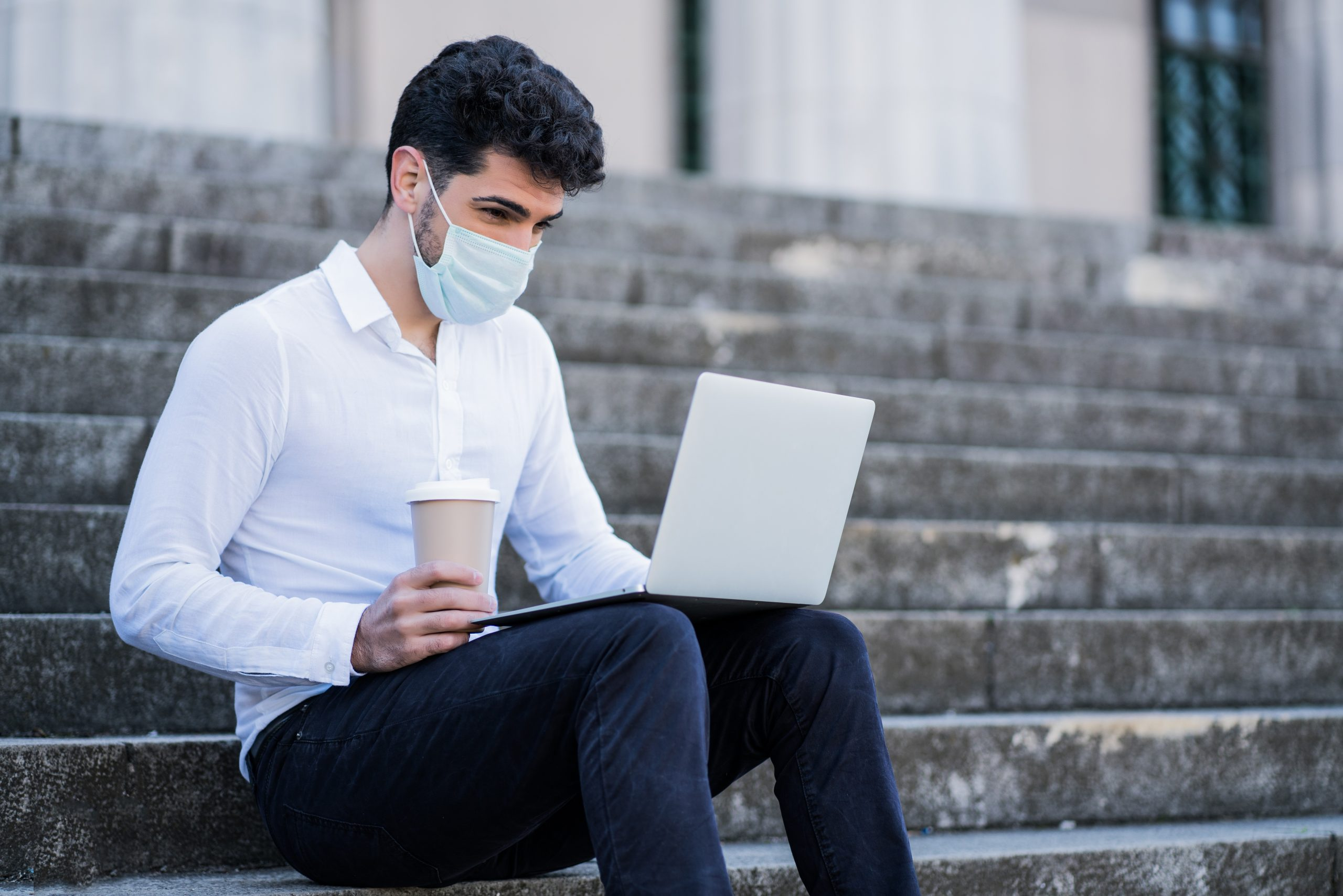 Portrait of business man wearing face mask and using his laptop while sitting on stairs outdoors. Business concept. New normal lifestyle concept.
